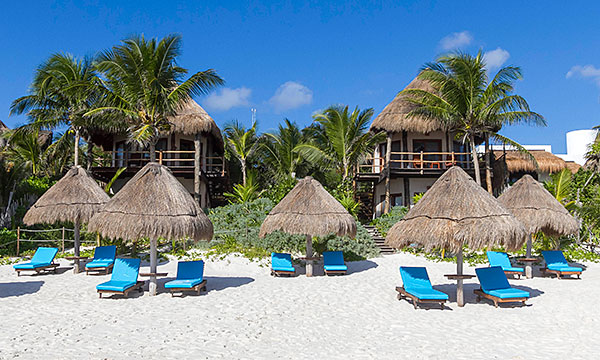 Beach huts with lounge chairs Mexico Tulum ecotourism